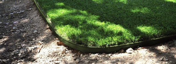 synthetic turf supplies green in shady areas where grass doesn't grow