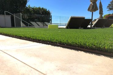 artificial turf edging provides border between turf and stamped concrete walkway